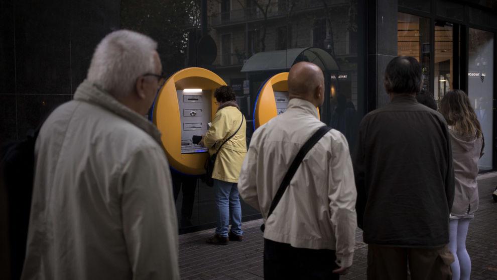 Folk sto i kø fredag morgen for å ta ut penger fra minibanker i Barcelona.