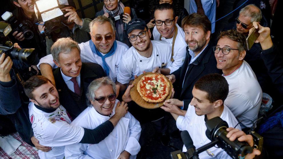 Italias kulturminister Dario Franceschini, andre fra høyre, holder en pizza bakt i den første steinovnen som ble brukt i 1889 til å lage den første pizza margaritaen i Napoli. Napolis pizzatradisjon har blitt lagt til i UNESCOs liste over immateriell kulturarv.