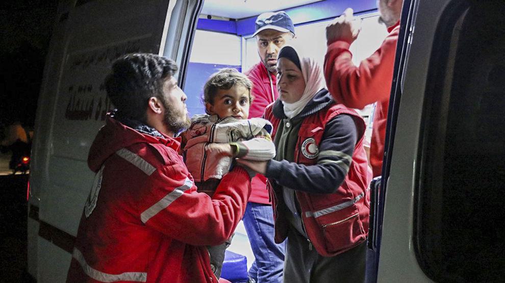 Medlemmer av Røde Halvmåne bærer en gutt som har flyktet sammen med familien sin fra kampene mellom regjeringsstyrker og Øst-Ghouta. Bildet ble offentliggjort av Røde Halvmåne tirsdag.