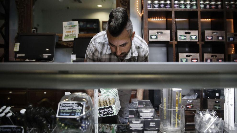 En ansatt på et cannabisutsalg i Los Angeles rydder i utsalgets produkter. Illustrasjonsfoto:
