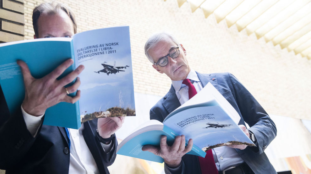 Stortinget vil få en redegjørelse og blir invitert til debatt om Norges krigsdeltakelse i Libya. Her leser NRK-journalist Sigurd Falkenberg Mikkelsen (t.v.) og Arbeiderparti-leder Jonas Gahr Støre i Libya-utvalgets rapport i Vandrehallen i Stortinget.