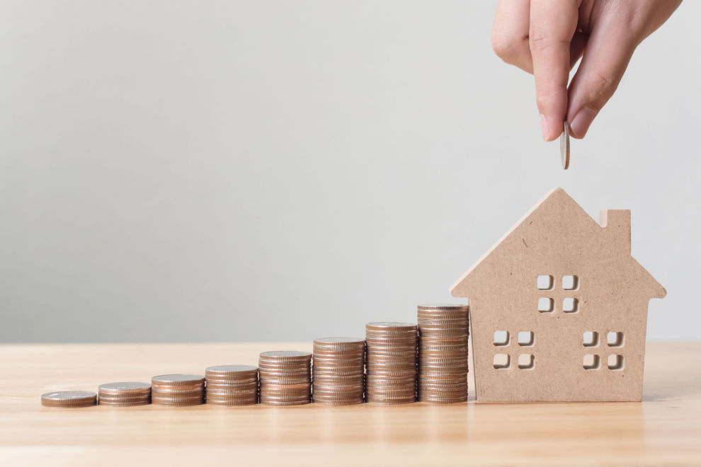 Property investment and house mortgage financial concept, Hand putting money coin stack with wooden house Property investment and house mortgage financial concept, Hand putting money coin stack with wooden house