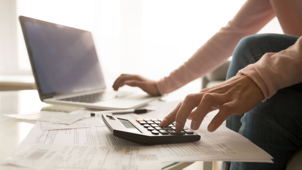 Close up of woman managing home utility bills Close up of woman sit at home using laptop and calculator analyze charges calculate monthly home expenses, focused female accounting consider or plan family budget, check utility bills in living room